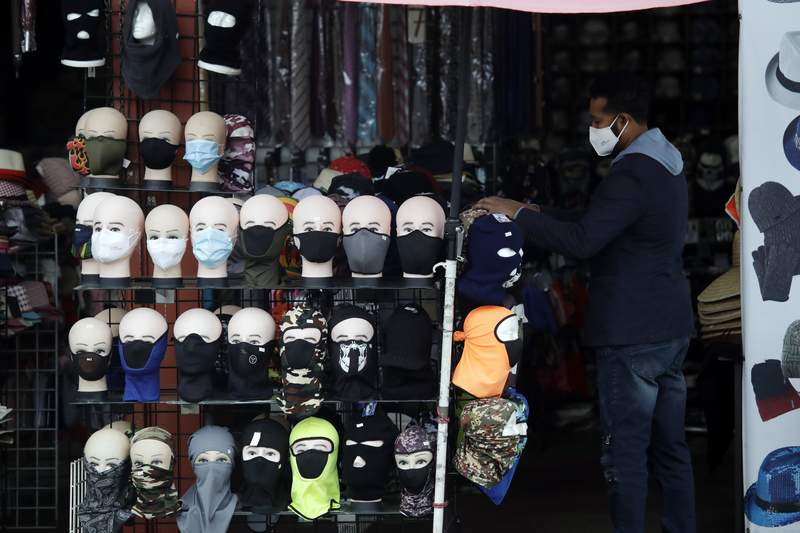 FILE - In this Friday, March 20, 2020, file photo, a merchant displays masks for sale in Los Angeles. Retail analysts expect mask sales will get another jolt after the Centers for Disease Control and Prevention late Tuesday, July 27, 2021, changed course on some masking guidelines, recommending that even vaccinated people return to wearing masks indoors in parts of the U.S. where cases of the coronavirus are surging. (AP Photo/Marcio Jose Sanchez, File)