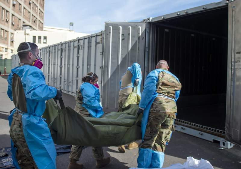 FILE - In this Jan. 12, 2021 photo provided by the Los Angeles County Department of Medical Examiner-Coroner, National Guard members assisting with processing COVID-19 deaths, placing them into temporary storage at the medical examiner-coroner's office in Los Angeles. The seven-day rolling average of daily deaths is rising in 30 states and the District of Columbia, and on Monday, Jan 18, 2021, the U.S. was approaching 398,000, according to data collected by Johns Hopkins University, by far the highest of any country in the world. (Los Angeles County Department of Medical Examiner-Coroner via AP, File)