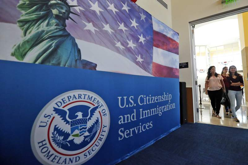 FILE - In this Aug. 17, 2018, file photo, people arrive before the start of a naturalization ceremony at the U.S. Citizenship and Immigration Services Miami Field Office in Miami. USCIS, The cash-strapped federal agency that oversees that nation's legal immigration system, scrapped plans Tuesday, Aug. 25, 2020, to furlough 13,000 employees, or nearly 70% of its workforce. The agency said it would maintain operations through September when the the fiscal year ends.  (AP Photo/Wilfredo Lee, File)