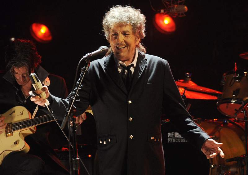 FILE - In this Jan. 12, 2012, file photo, Bob Dylan performs in Los Angeles. The music legend has quietly put concert tickets on sale for a tour in support of last year's album, Rough and Rowdy Ways. His website bills it as a World Wide Tour 2021-2024. (AP Photo/Chris Pizzello, File)