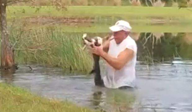 Richard Wilbanks wrestles his dog away from a gator.