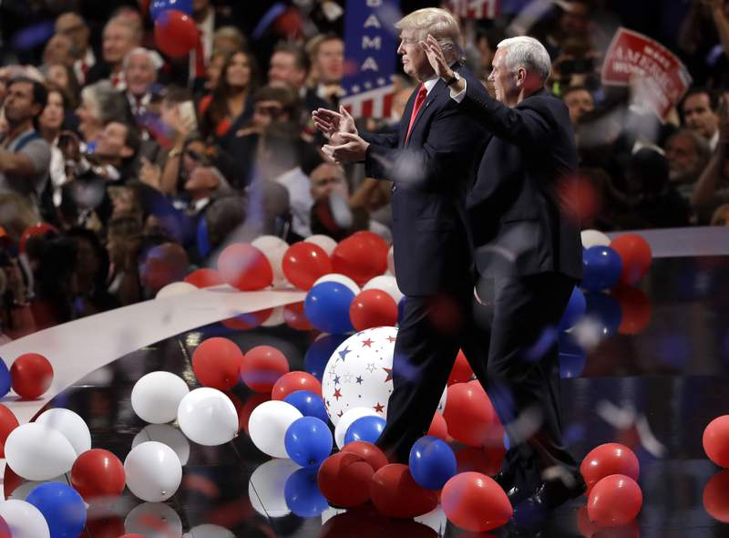 FILE - In this July 21, 2016, file photo Republican presidential candidate Donald Trump, center left, walks with vice presidential candidate Gov. Mike Pence of Indiana as confetti and balloons fall during celebrations after Trump's acceptance speech on the final day of the Republican National Convention in Cleveland. The coronavirus pandemic is forcing Democrats and Republicans to take a close look at whether they'll be able to move forward as planned this summer with conventions that typically kick off the general election season. (AP Photo/Matt Rourke, File)
