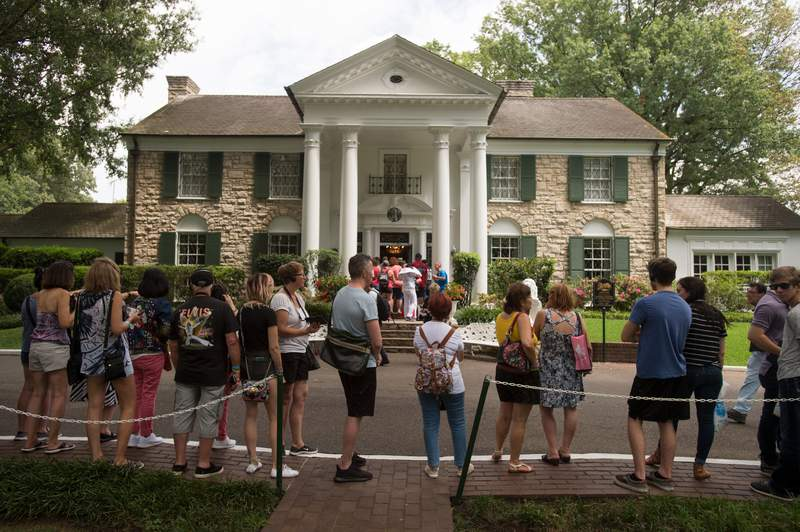 FILE - In an Aug. 15, 2017 file photo, fans wait in line outside Graceland, Elvis Presley's Memphis home, in Memphis, Tenn. Elvis Presleys Graceland says it will reopen Thursday, May 21, 2020 after it shut down tours and exhibits due to the new coronavirus outbreak. The tourist attraction in Memphis, Tennessee, said Sunday that it has adjusted its tours, and restaurant and retail operations, since it closed in March. (AP Photo/Brandon Dill, File)