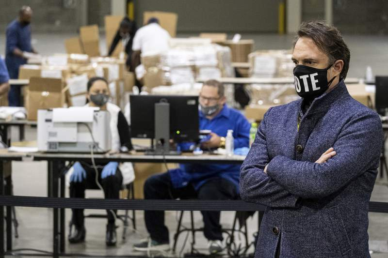 Fulton County Ga. election chief Richard Barron listens to a question during a press conference while workers scan ballots behind him as the presidential recount began.