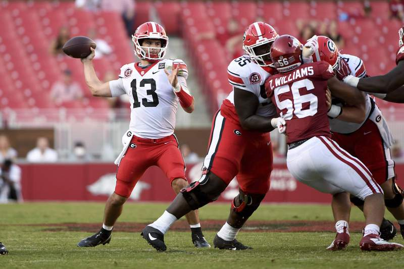 Georgia quarterback Stetson Bennett (13) throws a pass against Arkansas while offensive lineman Trey Hill (55) blocks during the second half of an NCAA college football game in Fayetteville, Ark., Saturday, Sept. 26, 2020. (AP Photo/Michael Woods)