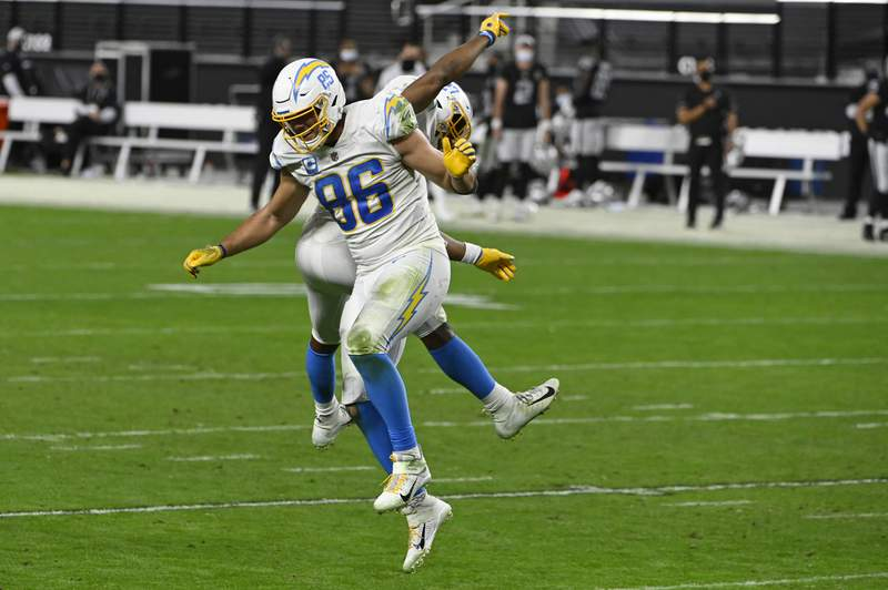Los Angeles Chargers tight end Hunter Henry (86) and running back Joshua Kelley (27) celebrate after a teammate recovered a Los Angeles Chargers fumble in overtime of an NFL football game against the Las Vegas Raiders, Thursday, Dec. 17, 2020, in Las Vegas. (AP Photo/David Becker)