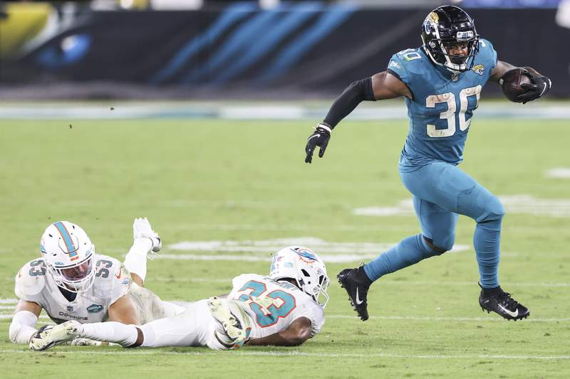 JACKSONVILLE, FLORIDA - SEPTEMBER 24: James Robinson #30 of the Jacksonville Jaguars runs for yardage against Jomal Wiltz #33 of the Miami Dolphins and Kyle Van Noy #53 during the third quarter of a game at TIAA Bank Field on September 24, 2020 in Jacksonville, Florida. (Photo by James Gilbert/Getty Images)