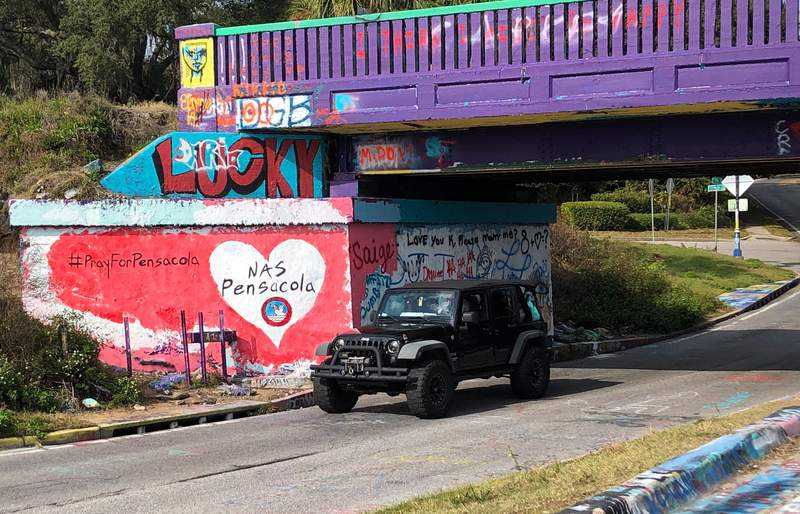 A vehicle drives by a tribute to victims of the Naval Air Station Pensacola that was freshly painted on whats known as Graffiti Bridge in downtown Pensacola, Fla., on Saturday, Dec. 7, 2019. (AP Photo/Brendan Farrington)