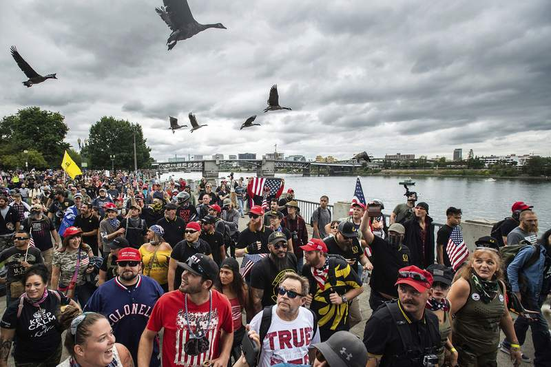FILE - In this Aug. 17, 2019, file photo, members of the Proud Boys and other right-wing demonstrators march along the Willamette River during a rally in Portland, Ore. Portland has denied a permit for a Saturday rally planned by the right-wing group Proud Boys. The Portland Parks & Recreation Bureau said Wednesday, Sept. 23, 2020, that the group's estimated crowd size of 10,000 people was too big under coronavirus safety measures.  (AP Photo/Noah Berger, File)