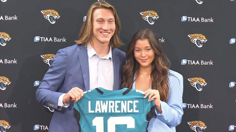 Trevor Lawrence and his wife, Marissa, pose with a jersey before sitting down to answer questions from Jacksonville reporters.