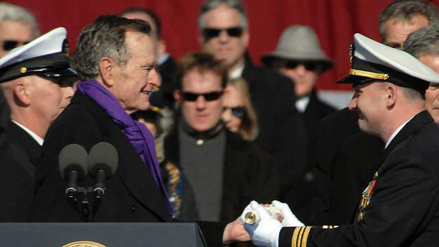 In this photo provided by the US Navy, Lt. Cmdr. George Brickhouse, assigned to the aircraft carrier USS George H.W. Bush accepts a long glass symbolizing the setting of the first watch from former President George H.W. Bush during the ship's commissioning ceremony at Naval Station January 10, 2009 in Norfolk, Virginia. George H.W. Bush delivered the keynote address at the commissioning. The Navy's newest, and final, Nimitz-class aircraft carrier is named after the World War II naval aviator and 41st president of the United States. (Photo by Micah P. Blechner/U.S. Navy via Getty Images)