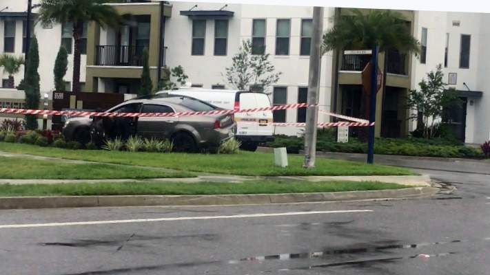 A person who was shot while driving crashed into the entrance of an apartment complex, police say.