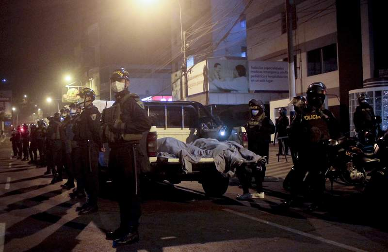 Police officers stand guard near two bodies outside of a disco in Lima, Peru, Sunday, Aug. 23, 2020. Officials said over a dozen people died in a stampede at a disco in Peru after a police raid to enforce the country's lockdown during the coronavirus pandemic. (AP Photo/Diego Vertiz)