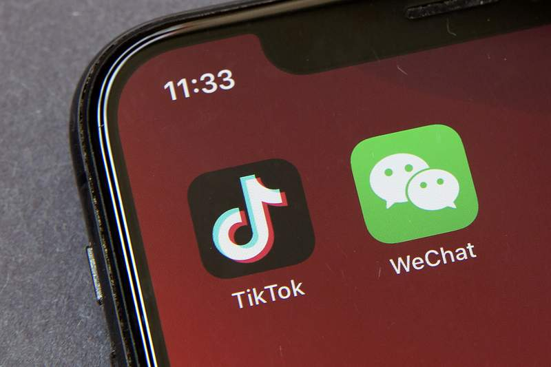FILE - Icons for the smartphone apps TikTok and WeChat are seen on a smartphone screen in Beijing, in a Friday, Aug. 7, 2020 file photo.  Officials say the White House has dropped Trump-era executive orders that attempted to ban the popular apps TikTok and WeChat and will conduct its own review aimed at identifying national security risks with software applications tied to China. A new executive order directs the Commerce Department to undertake what officials describe as an evidence-based analysis of transactions involving apps that are manufactured or supplied or controlled by China. Officials are particularly concerned about apps that collect users personal data or have connections to Chinese military or intelligence activities. (AP Photo/Mark Schiefelbein, File)