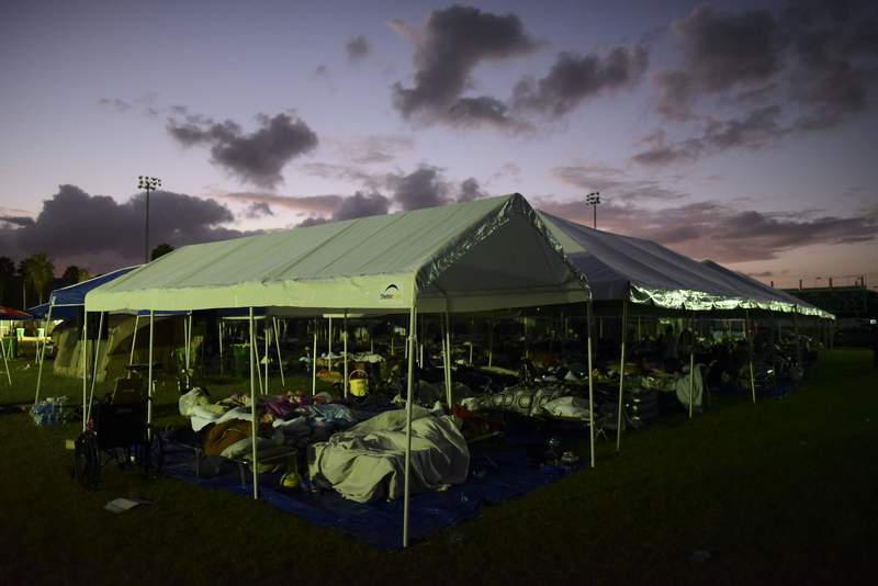 Tents and cots are set up for people whose homes are either destroyed or unsafe to enter after an 6.4 magnitude earthquake, at a baseball stadium amid aftershocks and no electricity in Guayanilla, Puerto Rico, at sunrise Friday, Jan. 10, 2020. Hundreds of thousands of Puerto Ricans are still without power and water, and thousands are staying in shelters and sleeping on sidewalks since Tuesdays earthquake. (AP Photo/Carlos Giusti)