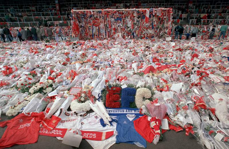 FILE - Liverpool soccer fans arrive at Anfield Stadium to pay their respects as flower tributes cover the 'Kop' end of the field, in Liverpool, on April 17, 1989, following April 15, when fans surged forward during the FA Cup semi-final between Liverpool and Nottingham Forest at Hillsborough Stadium in Sheffield, when the crash barriers gave way, killing 96 Liverpool fans and injuring over 200 others. A British judge has brought an end to a trial of two former police officers and an ex-lawyer on charges of perverting the course of justice in connection with the 1989 Hillsborough soccer disaster that saw 96 Liverpool fans die. Judge William Davis told jurors Wednesday, May 26, 2021 at a court in Salford, northwest England, that there was no case they could properly consider for the defendants. Donald Denton, an 83-year-old retired chief superintendent at West Yorkshire Police, former detective chief inspector Alan Foster, 74, and former solicitor Peter Metcalf, 71, had been charged of amending police statements following the disaster in an attempt to minimize blame on the force.( AP Photo, File)