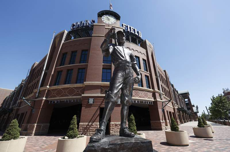 """The bronze statue entitled """"The Player,"""" by sculptor George Lundeen stands in front of the main gate of Coors Field, home of Major League Baseball's Colorado Rockies, Tuesday, June 23, 2020, in Denver. The league is waiting for the players' union to respond to whether it will agree to health protocols for a 60-game regular-season slate and if players will report for training camp by July 1. (AP Photo/David Zalubowski)"""