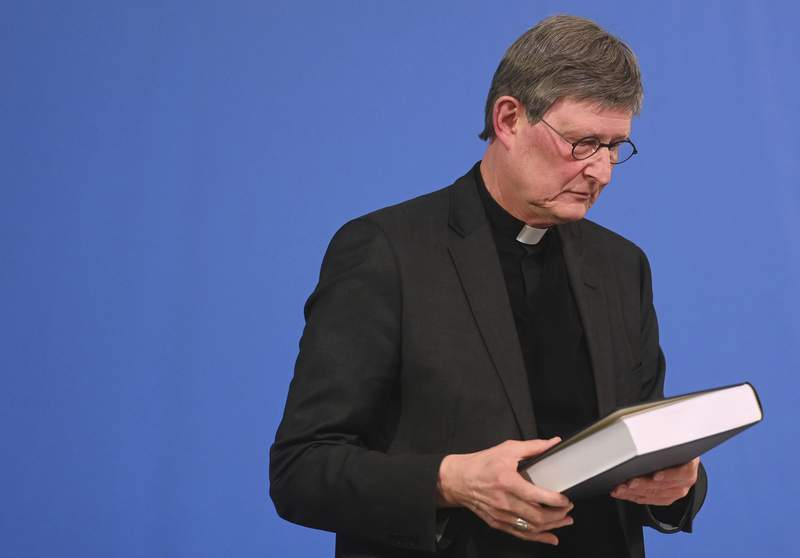Cologne's archbishop Cardinal Rainer Maria Woelki holds a report on abuse by clergy he had receives during a news conference in Cologne, Germany, Thursday, March 18, 2021. Faced with accusations of trying to cover up sexual violence in Germany's most powerful Roman Catholic diocese, the archbishop of Cologne publishes the independent investigation. (Ina Fassbender/Pool via AP)