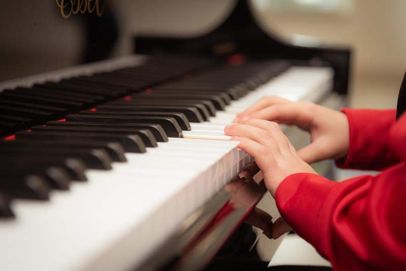 A child sits at a piano.