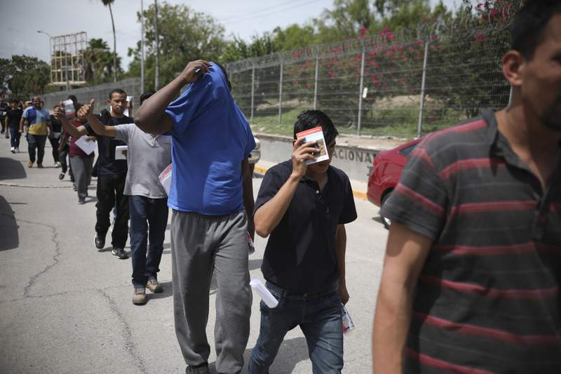 FILE - In this July 31, 2019, file photo, migrants return to Mexico, using the Puerta Mexico bridge that crosses the Rio Grande river in Matamoros, Mexico, on the border with Brownsville, Texas. A federal judge on Tuesday, Jan. 26, 2021, barred the U.S. government from enforcing a 100-day deportation moratorium that is a key immigration priority of President Joe Biden. U.S. District Judge Drew Tipton issued a temporary restraining order sought by Texas, which sued on Friday against a Department of Homeland Security memo that instructed immigration agencies to pause most deportations. Tipton said the Biden administration had failed to provide any concrete, reasonable justification for a 100-day pause on deportations. (AP Photo/Emilio Espejel, File)