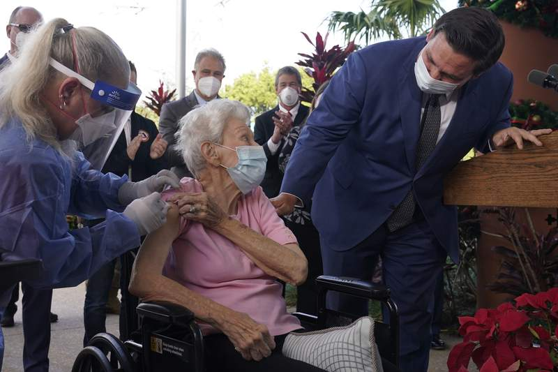 Florida Gov. Ron DeSantis asks Vera Leip, 88, how she feels after nurse Christine Philips, left, administered the Pfizer vaccine at John Knox Village, Wednesday, Dec. 16, 2020, in Pompano Beach, Fla. Nursing home residents and health care workers in Florida began receiving the Pfizer vaccine this week. (AP Photo/Marta Lavandier)