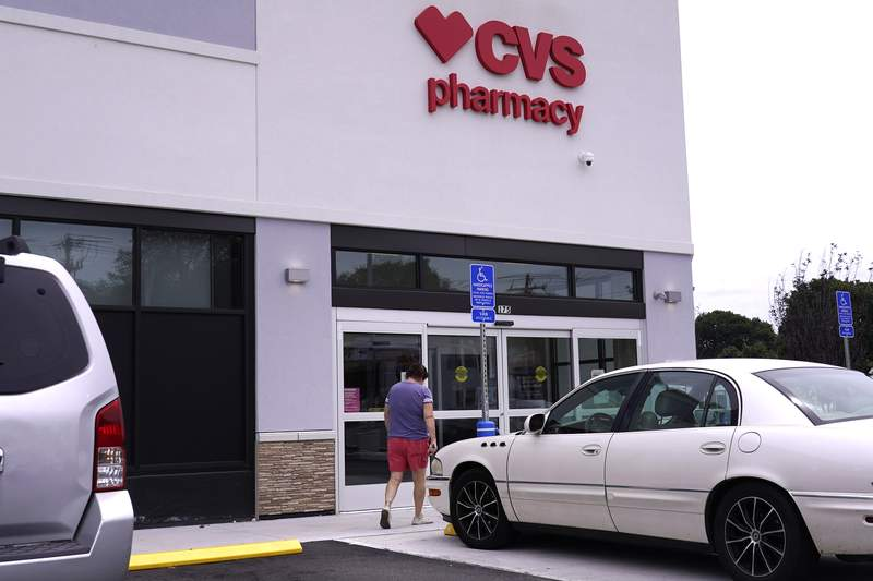 A customer walks into a CVS Pharmacy store, Tuesday, Aug. 3, 2021, in Woburn, Mass.  Customers returned to CVS Health stores to fill prescriptions and get COVID-19 tests and vaccines, helping to push the health care giant past Wall Streets second-quarter expectations.  (AP Photo/Charles Krupa)