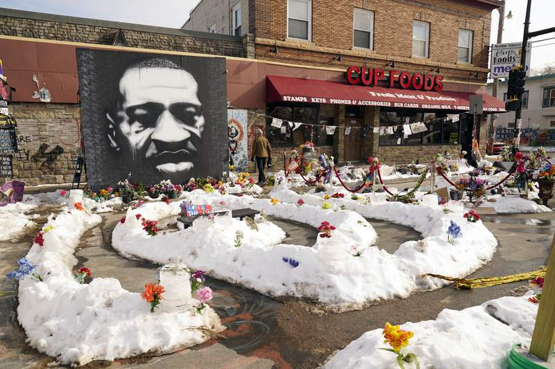 FILE - In this Feb. 8, 2021 file photo, A mural of George Floyd is seen in George Floyd Square in Minneapolis. The city of Minneapolis on Friday, March, 12, 2021, agreed to pay $27 million to settle a civil lawsuit from George Floyd's family over the Black man's death in police custody, as jury selection continued in a former officer's murder trial. The settlement includes $500,000 for the south Minneapolis neighborhood that includes the 38th and Chicago intersection that has been blocked by barricades since his death, with a massive metal sculpture and murals in his honor. (AP Photo/Jim Mone File)