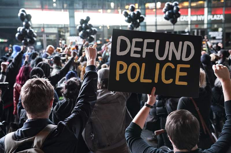 """FILE - In this Oct. 14, 2020, file photo a protester holds a sign that reads """"Defund Police"""" during a rally for the late George Floyd outside Barclays Center in New York. Some police organizations and Republican politicians are blaming Democrats and last year's defund the police effort for a troubling rise in homicides in many cities across the country. The increases are real, and some cities did make modest cuts to police spending. But the claims by Republicans overlook the fact homicides are up in many cities, including ones that increased police spending or have Republican mayors. (AP Photo/John Minchillo, File)"""