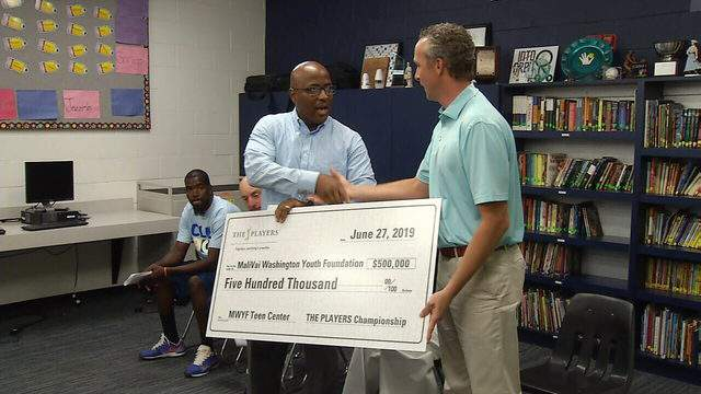 Former tennis star MaliVai Washington, left, shakes hands with Jared Rice, the executive director of The Players, on Thursday. Rice presented Washington with a $500,000 grant for the Teen Center, part of the foundation's new project that will open next year.