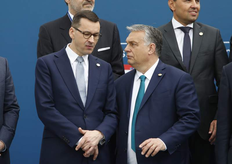 FILE - In this Feb. 1, 2020 file photo, Poland's Prime Minister Mateusz Morawiecki, left, and Hungary's Prime Minister Victor Orban share a word as they line up for a group picture prior to a meeting in Beja, Portugal. Polish government officials insisted on Friday, Dec. 4, 2020, that they are sticking to their tough negotiating position ahead of a key European Union summit next week that should finalize the blocs next seven-year budget and a major pandemic recovery package. (AP Photo/Armando Franca, File)