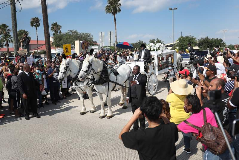HOUSTON, TEXAS - JUNE 09:  People watch as the horse drawn hearse containing the remains of George Floyd makes its way to the Houston Memorial Gardens cemetery on June 9, 2020 in Houston, Texas. Floyd died May 25 while in Minneapolis police custody, sparking nationwide protests. (Photo by Joe Raedle/Getty Images)