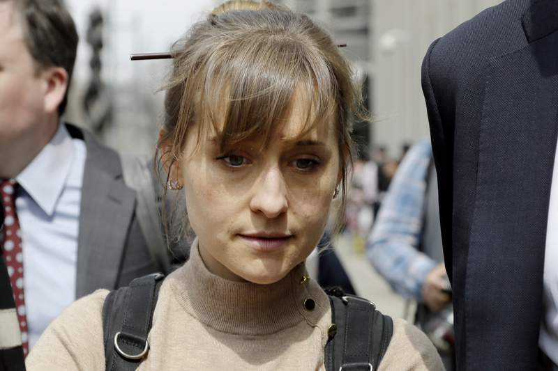 FILE-  In this April 8, 2019 file photo, actor Allison Mack leaves Brooklyn federal court in New York after pleading guilty to racketeering charges in a case involving a cult-like group based in upstate New York called NXIVM.  Mack, who played a key role in the cultlike group NXIVM, has surrendered to a California prison to serve her sentence in a New York case against the groups spiritual leader. (AP Photo/Mark Lennihan, File)