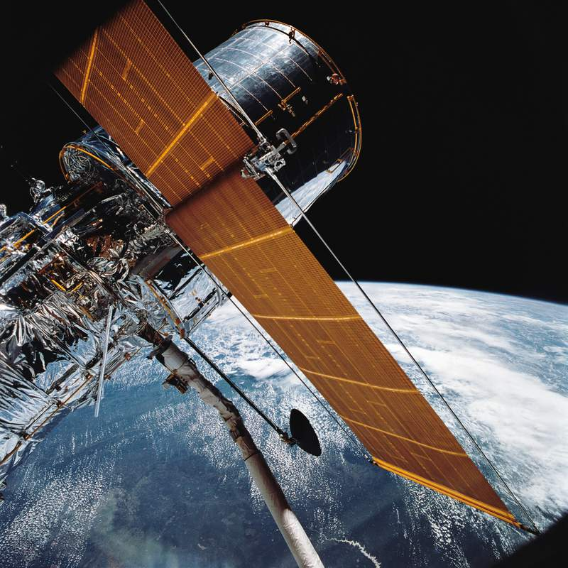 FILE - In this April 25, 1990 photograph provided by NASA, most of the giant Hubble Space Telescope can be seen as it is suspended in space by Discovery's Remote Manipulator System (RMS) following the deployment of part of its solar panels and antennae.   The Hubble Space Telescope should be back in action soon, Friday, July 16, 2021, following a tricky, remote repair job by NASA. The orbiting observatory went dark in mid-June, with all astronomical viewing halted. (NASA via AP)