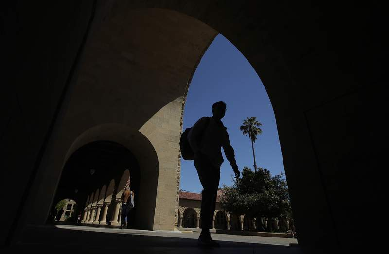 FILE - In this April 9, 2019, file photo, pedestrians walk on the campus at Stanford University in Stanford, Calif. The Education Department released a report Tuesday, Oct. 20, 2020, amid its effort to enforce a 1986 law requiring U.S. universities to disclose gifts and contracts from foreign sources. The departments findings are primarily based on investigations it has opened at 12 schools, including Harvard, Yale, Stanford and Georgetown universities. (AP Photo/Jeff Chiu, File)