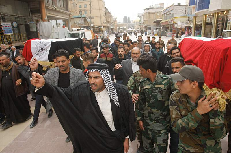 Mourners carry the flag-draped coffins of two fighters of the Popular Mobilization Forces who were killed during the US attack on against militants in Iraq, during their funeral procession at the Imam Ali shrine in Najaf, Iraq, Saturday, March 14, 2020. The U.S. launched airstrikes on Thursday in Iraq, targeting the Iranian-backed Shiite militia members believed responsible for a rocket attack that killed and wounded American and British troops at a base north of Baghdad. (AP Photo/Anmar Khalil)