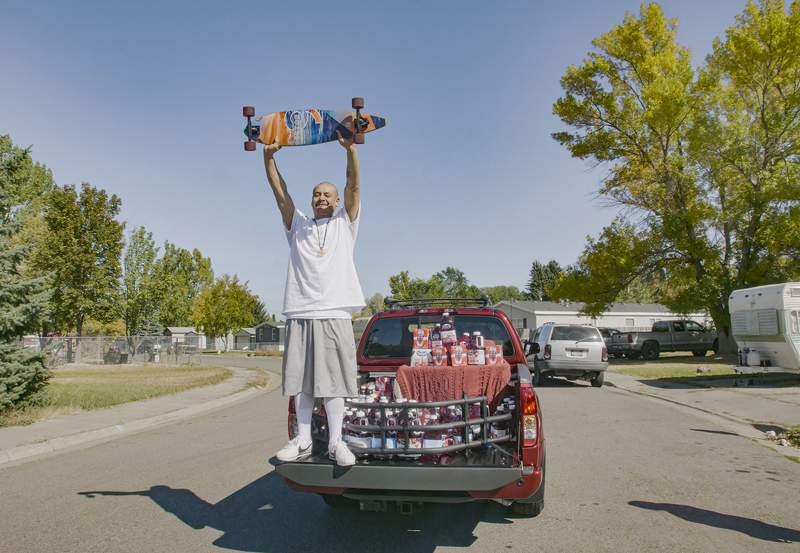 This Oct. 6, 2020 photo released by Ocean Spray shows  Nathan Apodaca holding his skateboard while standing in the back of a truck with Ocean Spray products in Idaho Falls, Idaho. Apodaca is enjoying fame from a 22-second TikTok video in which he chugs cranberry juice and sings along to Fleetwood Macs Dreams while cruising down an Idaho highway atop a longboard. The video has racked up 28 million views and counting since he posted it last month. Ocean Spray, whose juice Apodaca is seen swigging in the video, gave him a new truck stocked with juice this week. (Wesley White/Ocean Spray via AP)