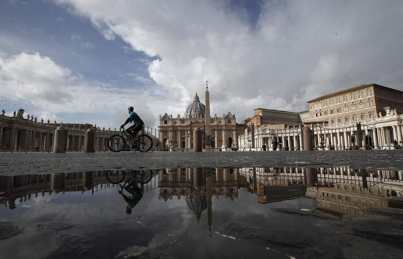 A cyclist is reflected on a puddle in an empty St.Peter's Square, as Pope Francis is reciting the Angelus noon prayer in his studio in the Apostolic palace, seen on the right, at the Vatican, Sunday, Jan. 31, 2021. (AP Photo/Alessandra Tarantino)