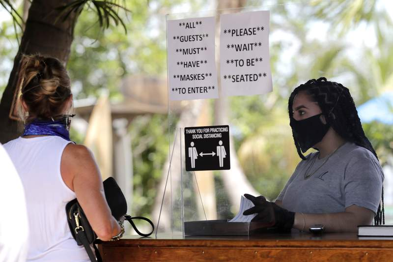 In this file photo, Nailea Rosales works behind a protective shield wearing a protective mask and gloves at the Morada Bay Beach Cafe in Islamorada in the Florida Keys during the new coronavirus pandemic.