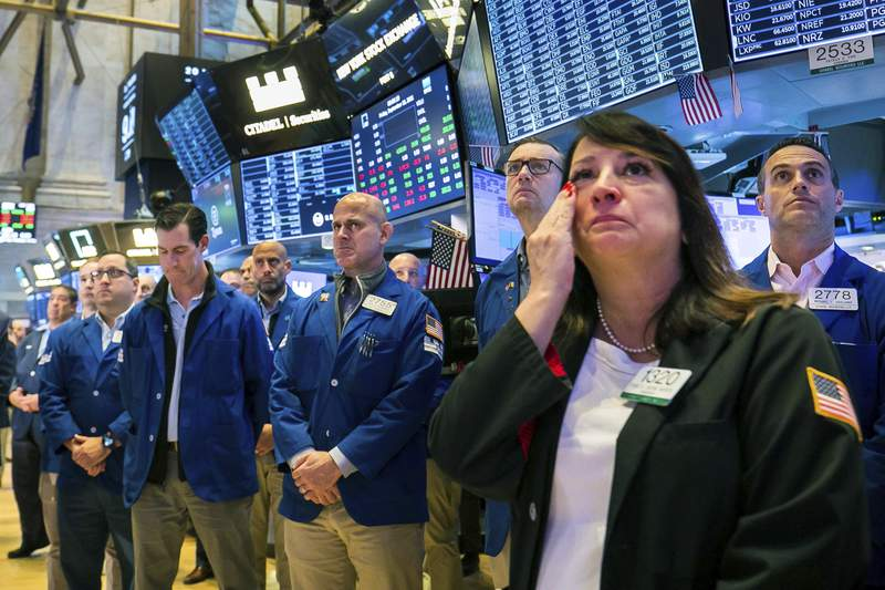 In this photo provided by the New York Stock Exchange, floor traders, including Phyllis Arena Woods, right, gather in remembrance on the eve of September 11th, on the Exchange trading floor, Friday Sept. 10, 2021. (Courtney Crow/New York Stock Exchange via AP)