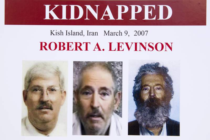FILE - In this March 6, 2012, file photo, an FBI poster showing a composite image of former FBI agent Robert Levinson, right, of how he would look like now after five years in captivity, and an image, center, taken from the video, released by his kidnappers, and a picture before he was kidnapped, left, displayed during a news conference in Washington. A federal judge has held Iran responsible for the kidnapping of former FBI agent Robert Levinson. U.S. District Judge Timothy Kelly entered a default judgement against the regime on the 13th anniversary on his disappearance. (AP Photo/Manuel Balce Ceneta, File)
