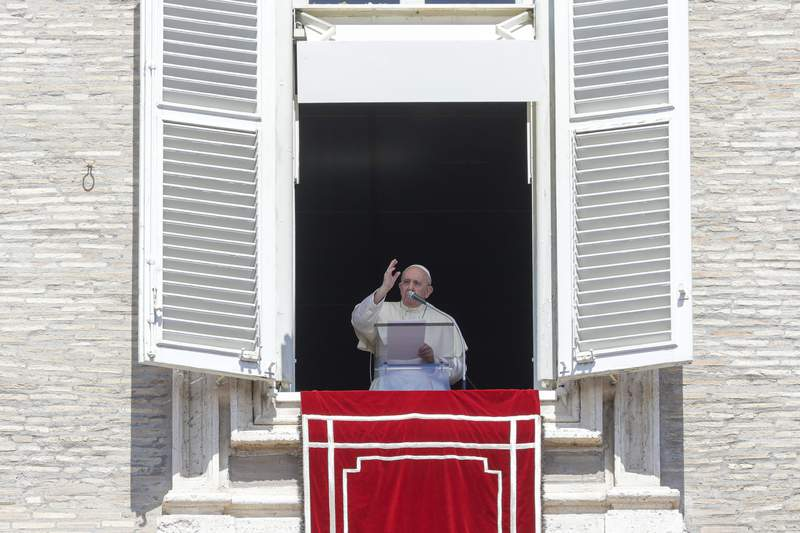 Pope Francis delivers his blessing as he recites the Angelus noon prayer from the window of his studio overlooking St.Peter's Square, at the Vatican, Sunday, Aug. 16, 2020. (AP Photo/Andrew Medichini)