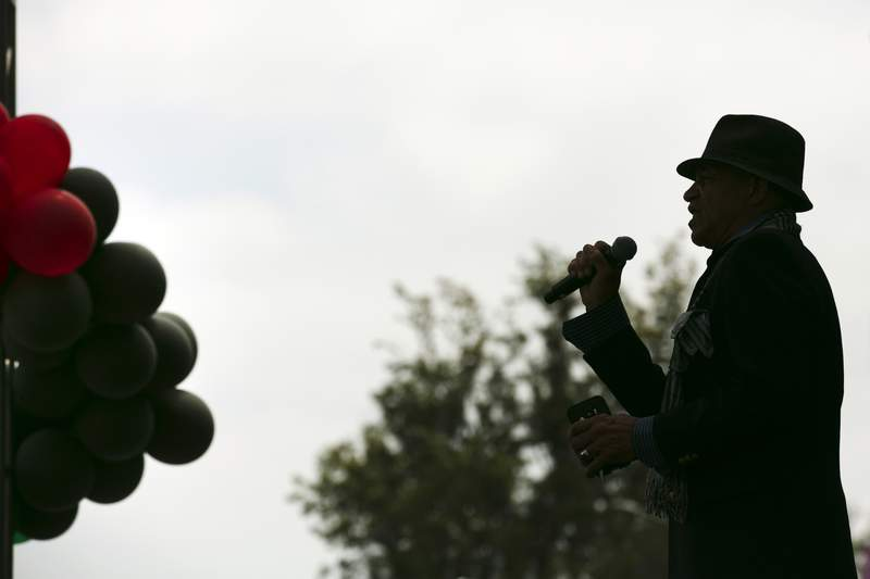 """In this June 19, 2020 file photo, Imani Abdul sings """"Lift Every Voice and Sing"""" during a Juneteenth celebration."""