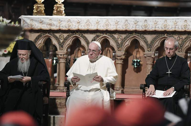FILE - In this uesday, Sept. 20, 2016 file photo, Pope Francis, center, flanked by Orthodox Patriarch of Constantinople Bartholomew I, left, and Canterbury Archbishop Justin Welby, pray together inside the Basilica of St. Francis, in Assisi, Italy.  The worlds major Christian leaders, Pope Francis, the Archbishop of Canterbury and the spiritual leader of the worlds Orthodox Christians, have issued a joint appeal for delegates at the Glasgow climate conference to listen to the cry of the Earth and make sacrifices to save the planet. The extreme weather and natural disasters of recent months reveal afresh to us with great force and at great human cost that climate change is not only a future challenge, but an immediate and urgent matter of survival, said the statement from Francis, Archbishop Justin Welby of the Anglican Communion and Patriarch Bartholomew I. (Tiziana Fabi/Pool Photo via AP)