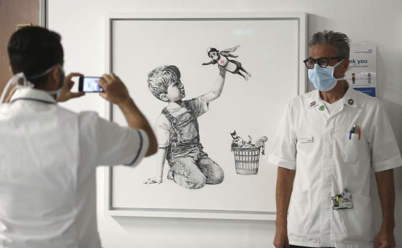 FILE - In this May 7, 2020 file photo, a member of staff has their photograph taken in front of the artwork painted by Banksy during lockdown, entitled 'Game Changer', at Southampton General Hospital in Southampton, England. A Banksy painting honoring Britains health workers in the coronavirus pandemic has sold for a record 16.8 million pounds ($23.2 million.) Auction house Christies said Tuesday, March 23, 2021 that proceeds from the sale will be used to fund health organizations and charities across the U.K. (Andrew Matthews/PA via AP, file)