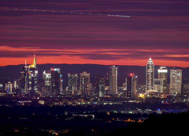 Long exposure photo shows an aircraft flying over the buildings of the banking district in Frankfurt, Germany, before sunrise on Sunday, Oct. 3, 2021. (AP Photo/Michael Probst)