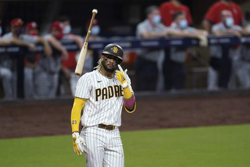 FILE - In this Oct. 1, 2020, file photo, San Diego Padres' Fernando Tatis Jr. tosses his bat after hitting a two-run home run during the seventh inning of Game 2 of the team's National League wild-card baseball series against the St. Louis Cardinals in San Diego. Tatis Jr. has yet to take a ground ball or swing a bat at spring training and he i already the talk of the Padres clubhouse. The electrifying shortstop and the Padres have agreed to a $340 million, 14-year deal, giving San Diegos camp even more buzz than it already had after the team made a number of high-profile offseason moves. (AP Photo/Gregory Bull, File)