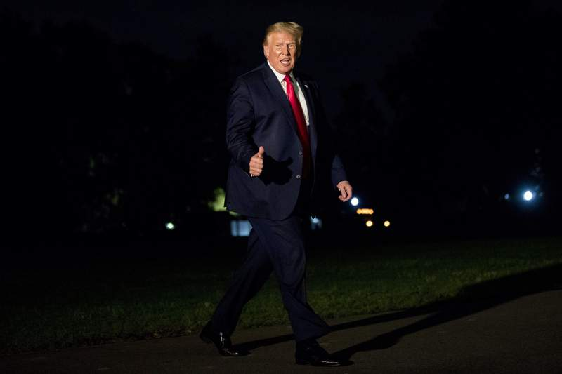 President Donald Trump gives a thumbs-up to members of the media as he walks across the South Lawn as he arrives at the White House in Washington, Sunday, Aug. 9, 2020, after returning from Morristown, N.J. (AP Photo/Andrew Harnik)