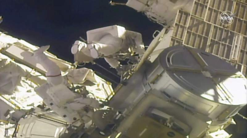 In this image taken from NASA video, NASA astronauts Mike Hopkins, left, and Victor Glover work outside the International Space Station on Monday, Feb. 1, 2021. The pair ventured out on their second spacewalk in under a week Monday to complete a four-year effort to modernize the International Space Station's power grid. (NASA via AP)