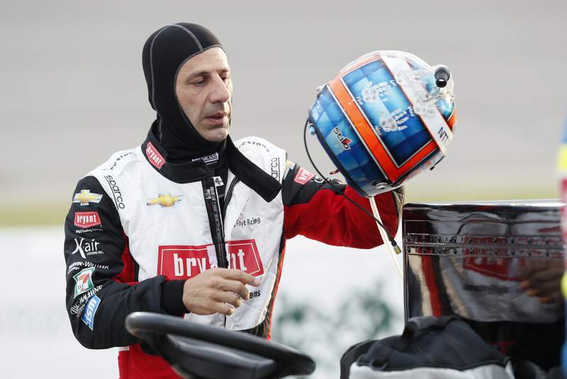 FILE - In this July 18, 2020 file photo, Tony Kanaan, of Brazil, puts on his helmet before the start of the IndyCar Series auto race at Iowa Speedway in Newton, Iowa.   Kanaan has another shot at a proper IndyCar farewell tour as the co-driver with Jimmie Johnson the next two years at Chip Ganassi Racing. The seven-time NASCAR champion signed on for the road and street course events, and Ganassi announced Monday, Nov. 23,  that Kanaan will complete the season in the No. 48 Honda.   (AP Photo/Charlie Neibergall)