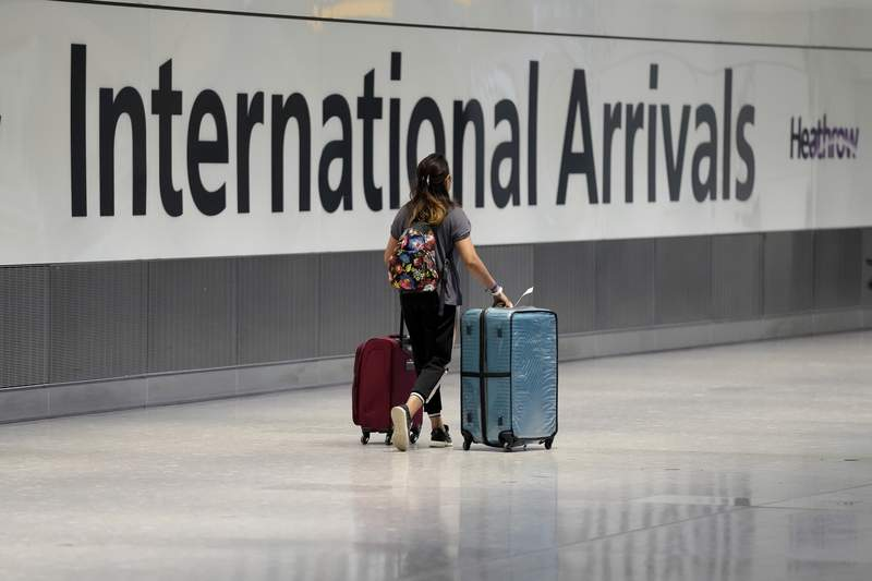 FILE - In this Monday, Aug. 2, 2021 file photo, a passenger arrives from a flight at Terminal 5 of Heathrow Airport in London. The British government said Thursday Oct. 7, 2021, that it is to relax travel rules further next week, a move that will open up many long-distance holiday destinations to travelers for the first time since the onset of the coronavirus pandemic a year and half ago. (AP Photo/Matt Dunham, File)
